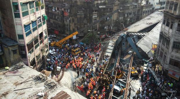 Locals and rescue workers clear the rubble of a partially collapsed overpass in Kolkata (AP)