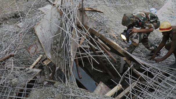 An Indian soldier looks for survivors after the overpass collapsed in Kolkata (AP)