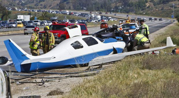 Emergency personnel investigate the scene of the plane crash on a California highway (The San Diego Union-Tribune/AP)