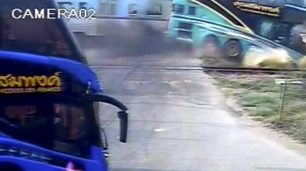 This image taken from close circuit television video shows the moment a passenger train hit a tourist bus at a crossing in Nakhon Pathom province, Thailand (TPBS via AP)