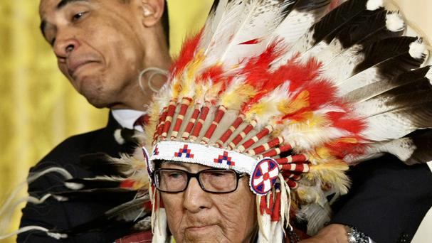 President Barack Obama leans away to avoid the headdress as he presents the 2009 Presidential Medal of Freedom to Joseph Medicine Crow (AP)