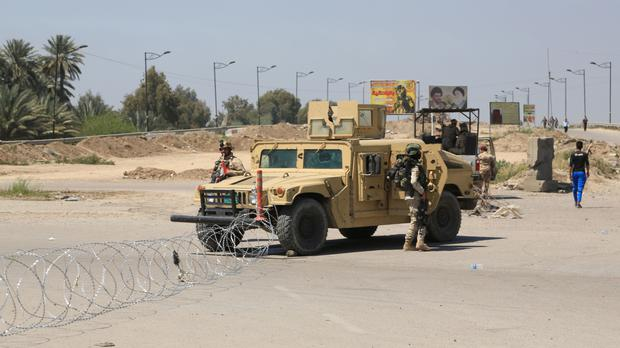 Iraqi army stand guard at the site near of a suicide attack targeting a checkpoint in Baghdad (AP)