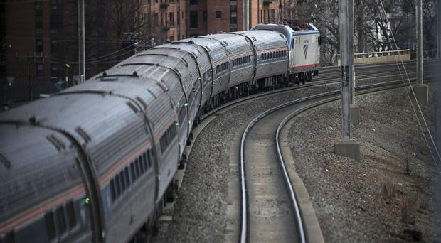 An Amtrak train passes through Elizabeth train station Saturday March 12 (AP)