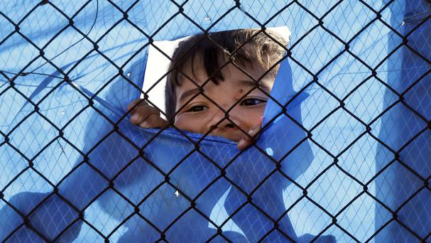 A migrant child looks out behind a wire fence of a refugee camp in the western Athens suburb of Schisto during the first day of the implementation of the deal between EU and Turkey
