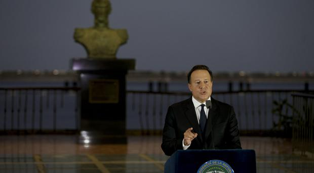 With a bust of Latin America's independence hero Simon Bolivar in the background, Panama's president Juan Carlos Varela gives a televised statement to the nation (AP)