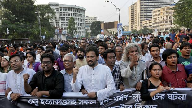 Protesters demand the arrest of three men who killed activist Nazimuddin Samad in Dhaka (AP)
