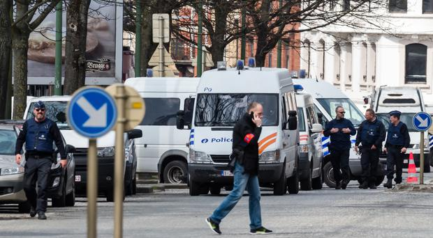 Police secure an area during a house search in the Etterbeek neighbourhood in Brussels on Saturday (AP)