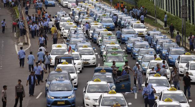 Taxis in Jakarta during a protest against competition from ride-hailing apps such as Uber and Grab (AP)