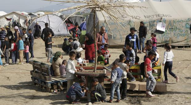 Migrants sit and drink tea at the northern Greek border point of Idomeni (AP)