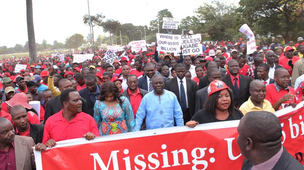 Opposition leader Morgan Tsvangirai joins party supporters as they march in Harare (AP)