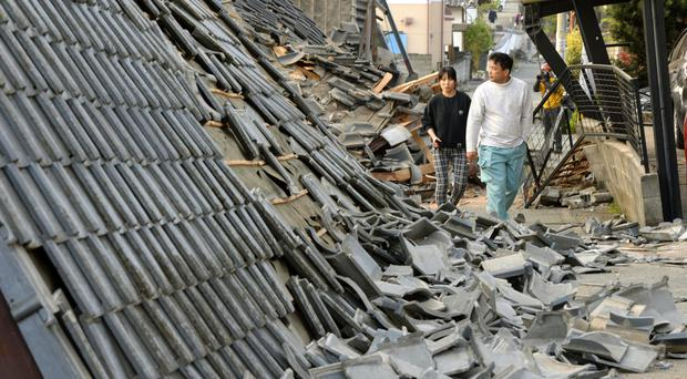 Residents pass collapsed houses in Mashiki after a powerful earthquake struck (Kyodo News/AP)