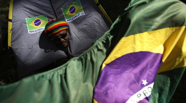 A demonstrator peeks out from his tent during a protest calling for the impeachment of Brazil's president Dilma Rousseff in Brasilia (AP)
