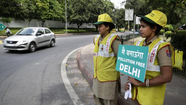Volunteers remind commuters of the reason for the car restriction in New Delhi (AP)