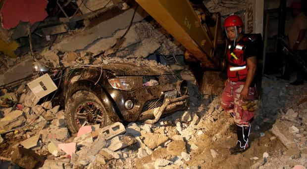 A rescue worker searches in the rubble of a destroyed house in the Pacific coastal town of Pedernales in Ecuador
