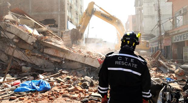 A rescue worker stands by as debris from a collapsed building in Portoviejo is moved (AP)