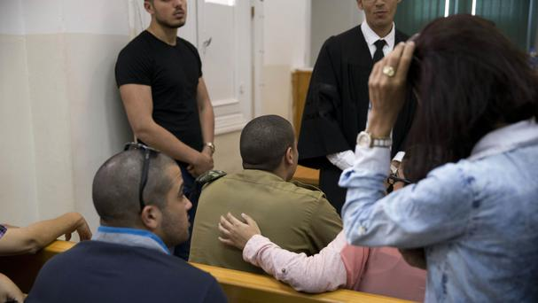 An Israeli soldier sits inside a military court in Tel Aviv (AP)