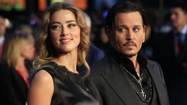 Amber Heard, pictured with husband Johnny Depp, avoided jail over the dog smuggling case