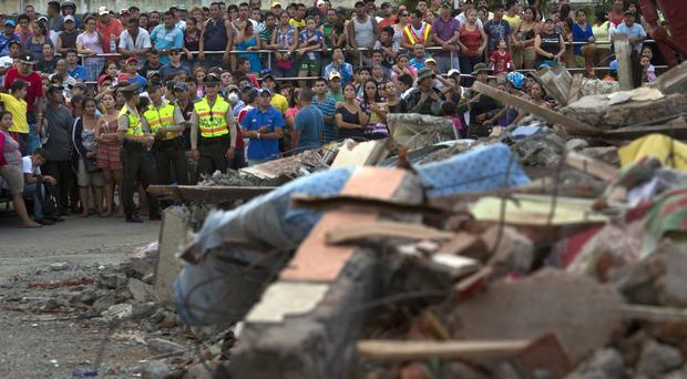 Anxious residents look on as rescue workers search the rubble of a collapsed building in Manta (AP)