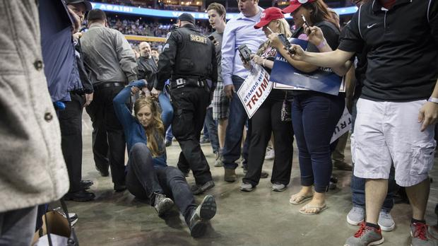 A protester is dragged away by authorities as Republican presidential candidate Donald Trump speaks during a campaign stop in Buffalo, New York (AP)