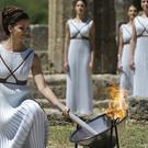 A dancer dressed as a priestess lights the Olympic flame in Ancient Olympia, Greece (AP)