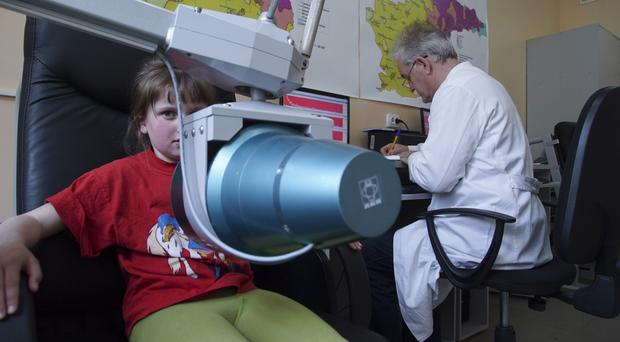 A paediatrician performs a yearly check for radioactive elements on a 10-year-old schoolgirl (AP)