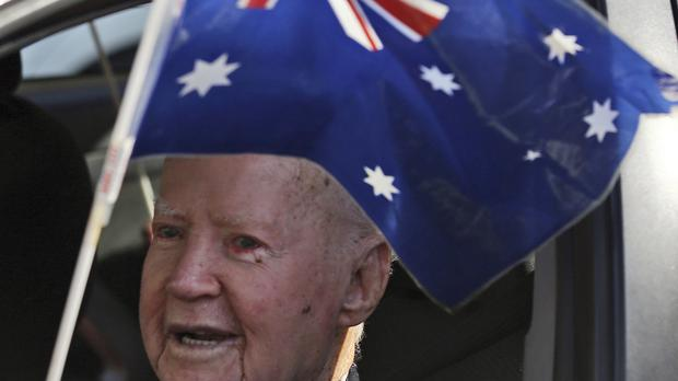 A war veteran waves the Australian national flag in the annual Australia and New Zealand Army Corps (Anzac) parade in Sydney (AP)