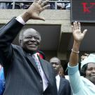 Kenyan president Mwai Kibaki and his wife Lucy wave to supporters in Nairobi in 2007 (AP)
