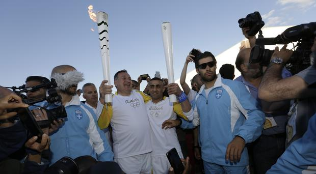 Syrian refugee Ibrahim Al-Hussein receives the Olympic flame from the head of Greece's Olympic committee Spyros Capralos at the Elaionas camp (AP)