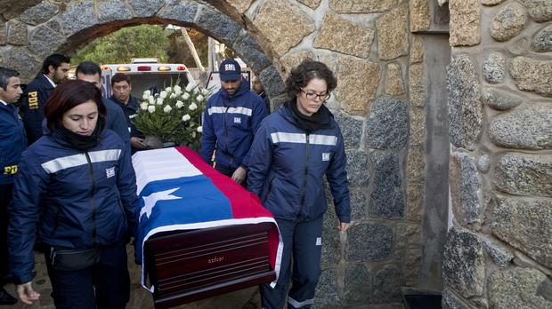 Forensic Institute workers carry a flag-draped coffin holding the remains of Pablo Neruda to the poet's home for reburial on Isla Negra, Chile (AP)