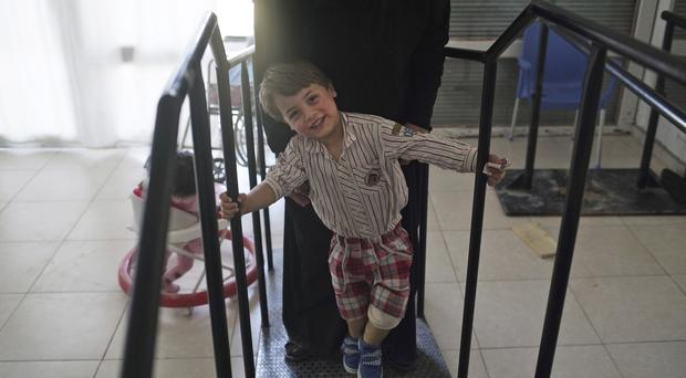 Three-year-old Seif, last name not available, smiles as he tries to walk using his two new prosthetic limbs with the help of his mother (AP)