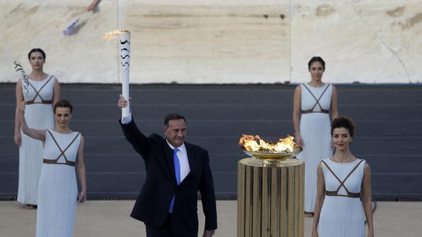 The head of Greece's Olympic Committee, Spyros Capralos, holds the torch with the Olympic flame, in Athens (AP)