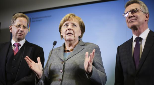 German Chancellor Angela Merkel stands between Hans-Georg Maassen, left, and interior minister Thomas de Maiziere (AP)