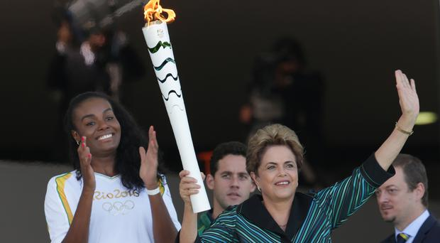 Brazil's president Dilma Rousseff holds the Olympic torch as Brazilian volleyball player Fabiana Claudino applauds after the torch was ignited at Planalto presidential palace (AP)