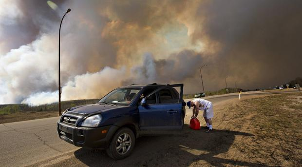 A man puts petrol in his car on his way out of Fort McMurray as the wildfire burns in the background (The Canadian Press /AP)