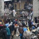 People help survivors retrieve their household items at the site of a building collapse in Nairobi (AP)