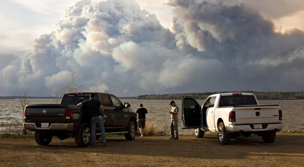 Evacuees watch the wildfire near Fort McMurray