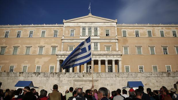 Protesters raise a Greek flag during an anti-austerity rally in front of the parliament in Athens (AP)