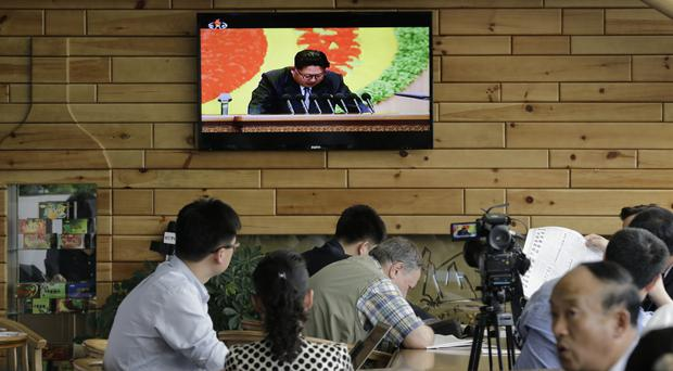Foreign journalists, who must cover the congress from outside the hall, take notes as North Korean leader Kim Jong Un speaks (AP)