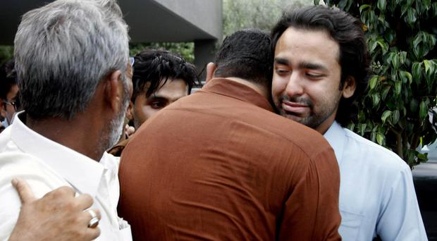 People embrace Musa Gilani, right, the brother of Ali Haider Gilani who was kidnapped (AP)