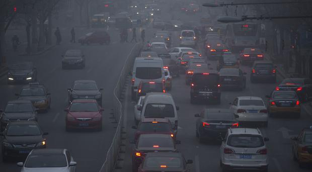 Pedestrians make their way across a busy road on a day with severe air pollution in Beijing (AP)