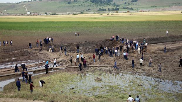 People surround the site of an explosion in the Sarikamis district outside Diyarbakir, Turkey (AP)
