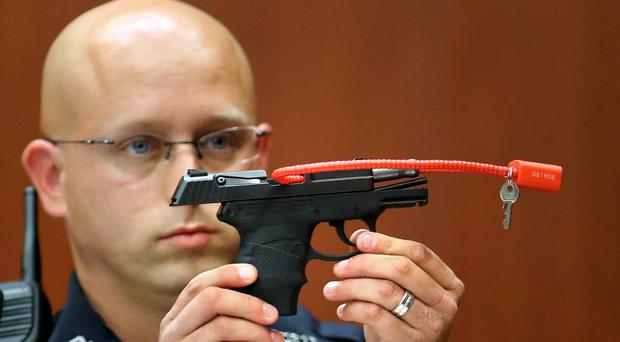 A police officer holds up the gun that was used to kill Trayvon Martin (AP)