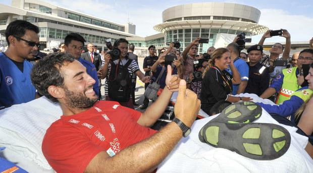 David Hernandez gives a thumbs up as he is stretchered away upon his arrival at the Kota Kinabalu International Airport in Sabah, Malaysia (AP)