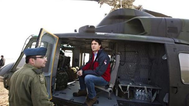 Prime Minister Justin Trudeau prepares to take a helicopter tour of the devastation during a visit to Fort McMurray (Jason Franson/The Canadian Press via AP)