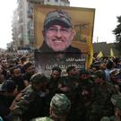 Hezbollah supporters carry the picture of their dead commander Mustafa Badreddine (AP)