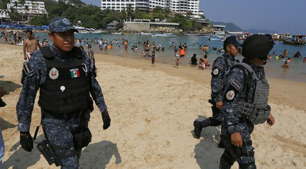 Federal police patrol Caleta beach in Acapulco, Mexico (AP)