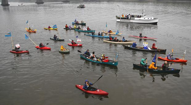 Opponents of oil trains and barges that service the Port of Albany paddle along the Hudson River in Albany, New York (AP)