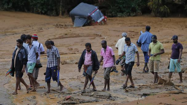 A rickshaw lies buried in the mud behind as villagers move to safety after the landslide in Elangipitiya (AP)