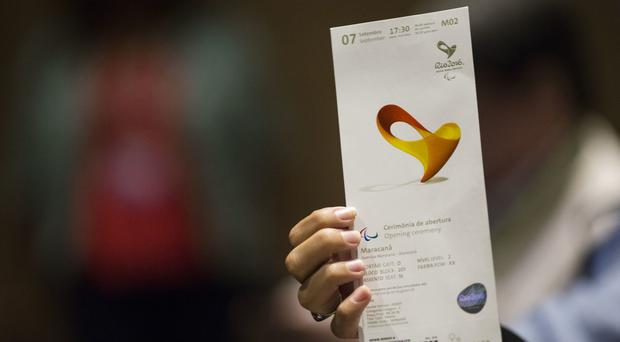 A journalist shows the Olympic ticket she won during a news conference where the design of Games tickets was unveiled (AP)