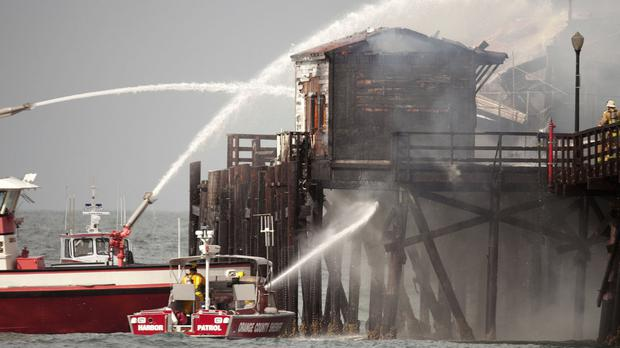 Firefighters tackled the flames from boats and from the pier itself (AP)